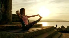 En ung kvinna med ett spensligt diagram är förlovad i gymnastik på havet på solnedgångkonturn stock video