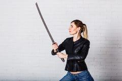 En ung kvinna med ett stort svärd arkivbild