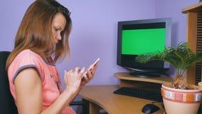 En ung kvinna med en förvånad och rubbningframsida använder en mobiltelefon arkivfilmer