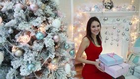 En ung kvinna med julgåvor sitter vid spisen i inre för ` s för det nya året stock video