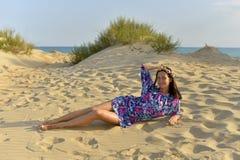 En ung kvinna med en krans av blommor på hennes huvud som vilar på en sandig strand royaltyfria foton