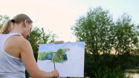 En ung kvinna med långt hår, som framkallar i vinden, målar en bild på kanfas, som står på staffli Damen arkivfilmer