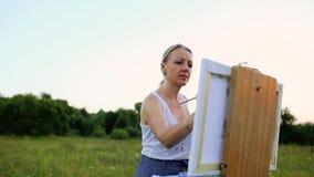 En ung kvinna med långt hår, som framkallar i vinden, målar en bild på kanfas, som står på staffli Damen stock video