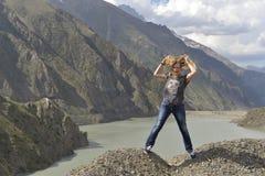 En ung kvinna med lurviga hårskratt, medan stå på kanten av en klippa ovanför en sjö arkivfoton