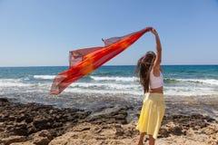 En kvinna med pareoen är på en segla utmed kusten Royaltyfri Fotografi