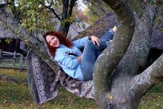 En ung kvinna med rött hår och ett härligt leende ligger på en filt som är spridning på ett träd Leenden och blickar in i kameran arkivfoton