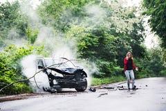 En ung kvinna med smartphonen vid den skadade bilen efter en bilolycka som gör en påringning royaltyfri fotografi