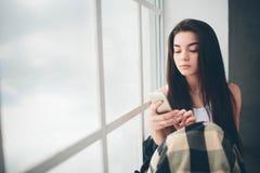 En ung kvinna med svart hår i en vit T-tröja på ett fönster som översvämmas med solljus, använder en smartphone, meddelar och Arkivbilder