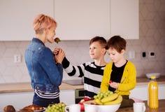 En ung kvinna med två barn som äter frukt i ett kök arkivbild
