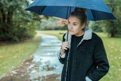 En ung kvinna med v?ntande p? b?ttre v?der f?r paraply royaltyfria bilder