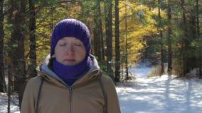 En ung kvinna mediterar i en snöig vinterskog på en solig dag lager videofilmer