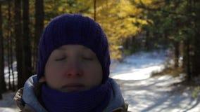 En ung kvinna mediterar i en snöig vinterskog på en solig dag arkivfilmer