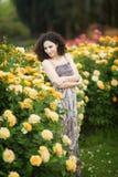 En ung kvinna nära busken för gula rosor som ser till det vänstert till och med en skuldra royaltyfri bild