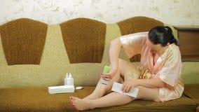 En ung kvinna på en soffa tar bort vaxet från huden av hennes ben med en servett stock video