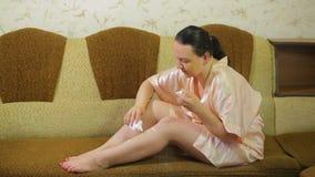 En ung kvinna på soffan applicerar hemma talkpulver på huden av hennes ben efter depilation lager videofilmer