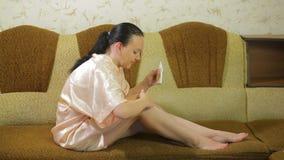 En ung kvinna på soffan applicerar hemma talkpulver på huden av hennes ben efter depilation stock video
