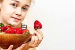 En ung kvinna rymmer en bunke av jordgubbar royaltyfria bilder