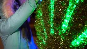 En ung kvinna rymmer hennes hand över en glödande festlig boll i gatan i vinter stock video