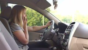 En ung kvinna sitter bak hjulet av en bil och talar på telefonen stock video
