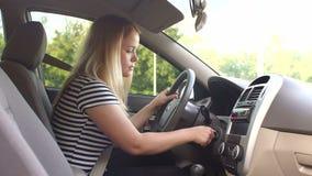 En ung kvinna sitter bak hjulet av en bil och vever upp tändningtangenten lager videofilmer
