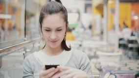 En ung kvinna sitter i ett offentligt ställe, genom att använda hennes telefon och le arkivfilmer