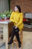 En ung kvinna sitter i köket i en gul stucken tröja Begreppshem, komfort, livsstil, höst, vinter fotografering för bildbyråer