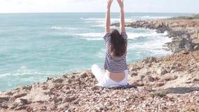 En ung kvinna sitter i en lotusblommaposition p? en klippa vid havet lager videofilmer