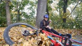 En ung kvinna sitter i en parkera, når han har fallit från en cykel, lugnar smärta i hennes knä, är en farlig cykelritt i parkera arkivfilmer