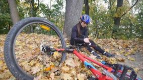 En ung kvinna sitter i en parkera, når han har fallit från en cykel, lugnar smärta i hennes knä, är en farlig cykelritt i parkera lager videofilmer