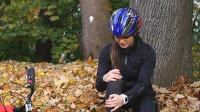 En ung kvinna sitter i en parkera, når han har fallit från en cykel, lugnar smärta i hennes knä, är en farlig cykelritt i parkera stock video