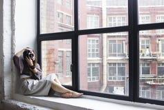 En ung kvinna sitter på en fönsterbräda med stora fönster och tagande Royaltyfria Bilder