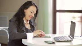 En ung kvinna sitter på en tabell i ett kafé med en bärbar dator och en minnestavla som bläddrar platsen Långsam mo
