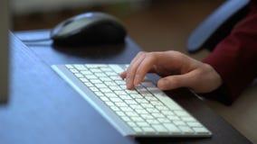 En ung kvinna som arbetar på ett skrivbord med ett datortangentbord arkivfilmer
