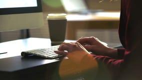 En ung kvinna som arbetar på ett skrivbord med ett datortangentbord långsam rörelse lager videofilmer