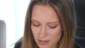 En ung kvinna som bär ett omslag i hennes kontor close upp arkivfilmer