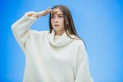 En ung kvinna som bär en vintertröja på en isolerad blå bakgrund, utan att le som lyfter hennes hand upp från, smärtar fotografering för bildbyråer