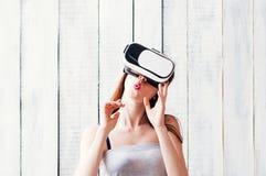 En ung kvinna som bär VR-exponeringsglas som rymmer hennes händer på framsidan, whi royaltyfri foto