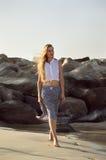 En ung kvinna som går på sjösidan Arkivfoto