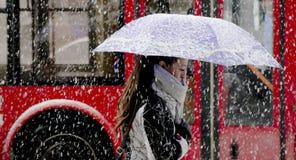 En ung kvinna som går under paraplyet i tungt snöfall i stadsgata royaltyfri foto