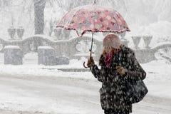 En ung kvinna som går under paraplyet i tungt snöfall i stadsgata vid, parkerar fotografering för bildbyråer