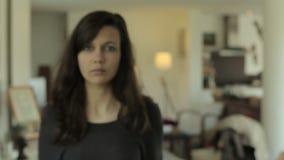 En ung kvinna som kommer in i en vardagsrum arkivfilmer