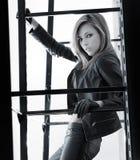 En ung kvinna som poserar i svart läderkläder Arkivfoton