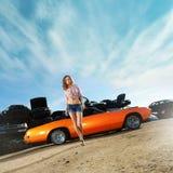 En ung kvinna som poserar nära en orange muskelbil Arkivfoton