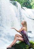 En ung kvinna som poserar på en vattenfallbakgrund Royaltyfri Bild