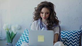 En ung kvinna som pratar med vänner i internet på en bärbar dator stock video