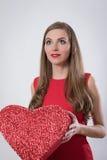 En ung kvinna som rymmer en stor röd hjärta Arkivbilder