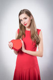 En ung kvinna som rymmer en stor röd hjärta Fotografering för Bildbyråer