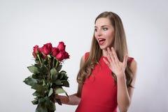 En ung kvinna som rymmer en stor rosbukett Royaltyfria Bilder