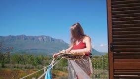 En ung kvinna som sätter våt kläder ut på ett rep för att torka det stock video