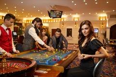 En ung kvinna som sitter på tabellrouletten som spelar poker på en kasino royaltyfri bild